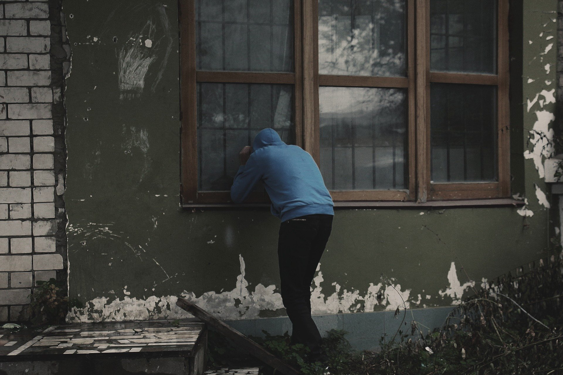 窓から泥棒が侵入しようとする様子